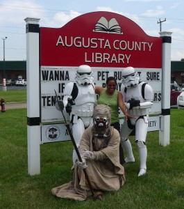 People dressed in Star Wars costumes in front of Fishersville Library sign